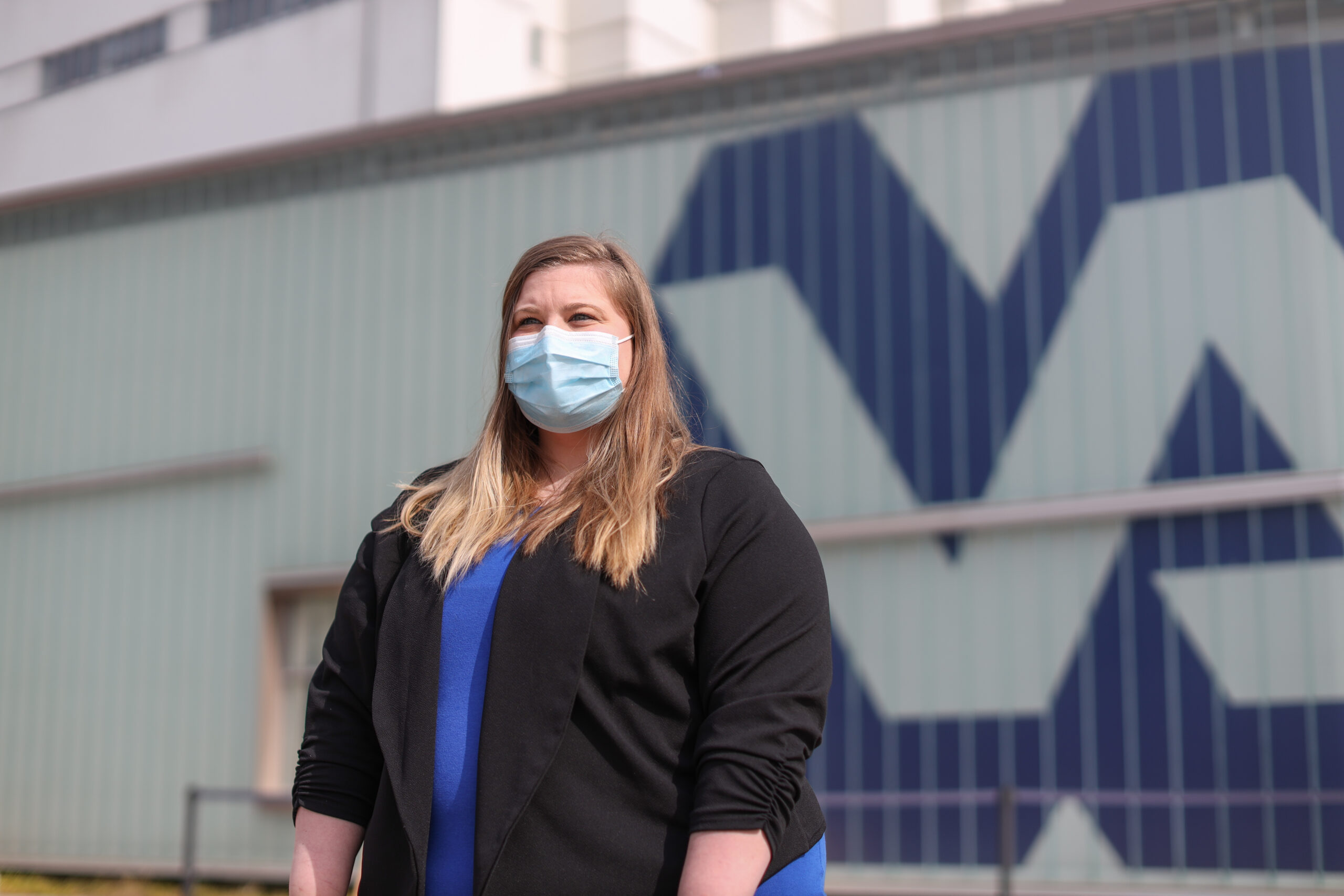 http://Katherine%20wearing%20a%20black%20sweater%20and%20blue%20shirt,%20and%20wearing%20a%20face%20mask%20standing%20outside%20with%20a%20building%20behind%20her