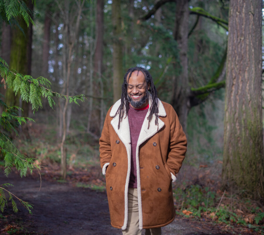 Tony wearing a brown and white coat smiling and standing in front of many green trees