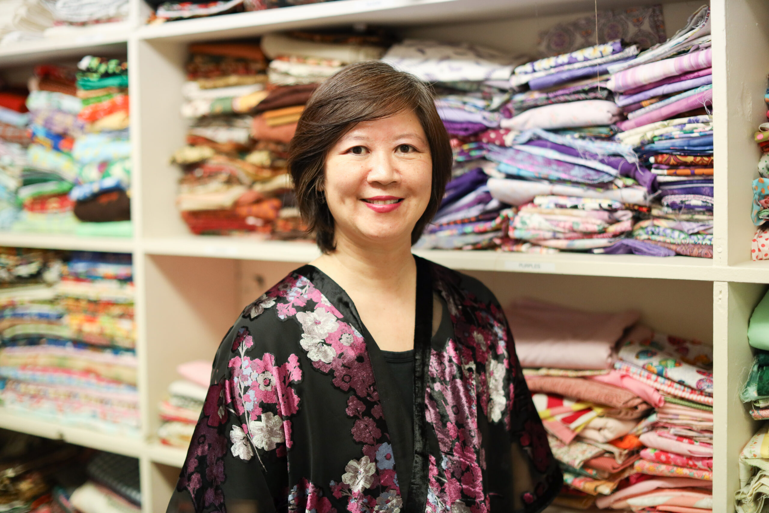 Ming-Ming wearing a black top with pink and white flowers standing in front of shelves of colored fabric.